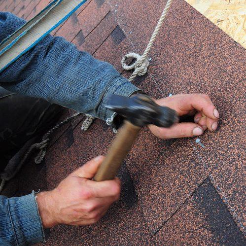 Close Up of Roofer Installing Asphalt Shingles