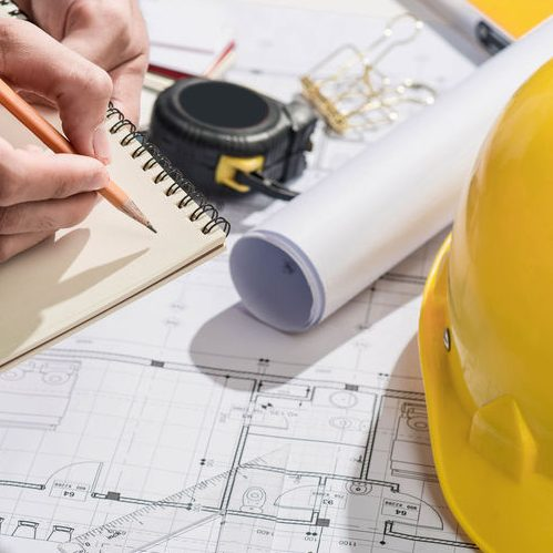 Blueprints of Construction, Hard Hat, Measuring Tape, Hand Taking Notes
