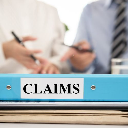 Insurance Claim Documents in Folders With Lawyers in a Meeting