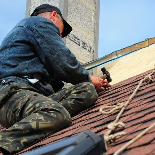 Worker on Roof Hammering Materials
