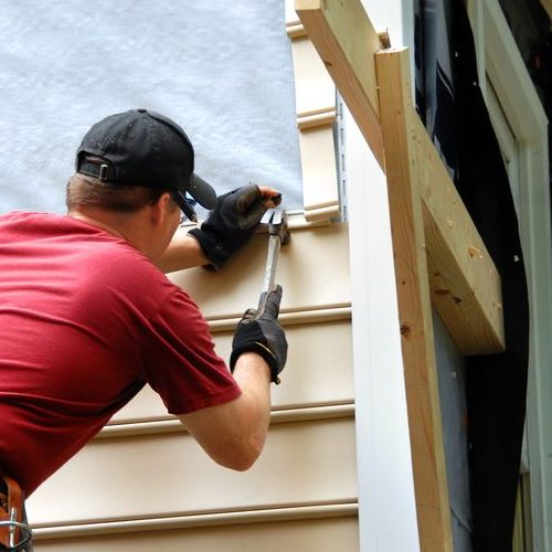 Worker Installing Siding With Hammer & Nails